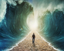 Man walking through the ocean with large waves on either side.
