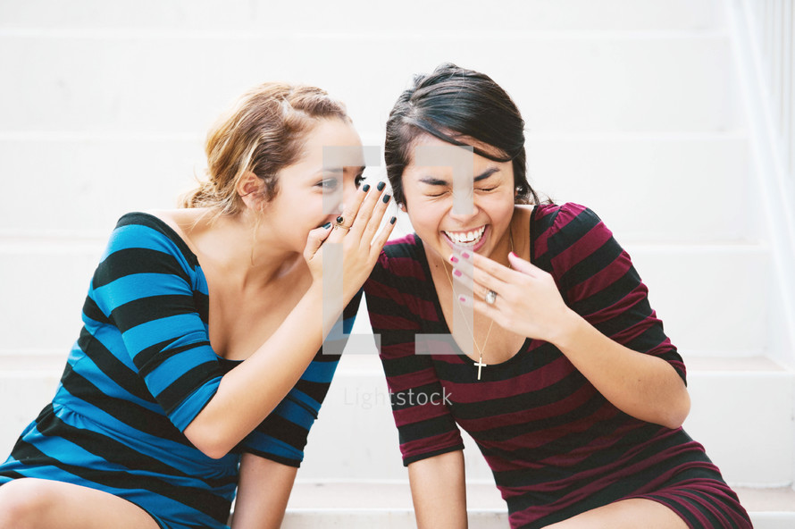 Two girls telling secrets and laughing, sitting on floor