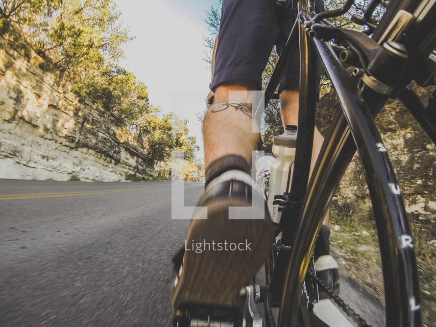 Feet pedalling a bike uphill.