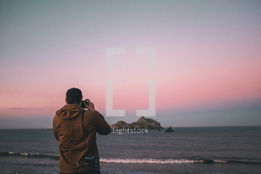 a man standing on a beach at sunset taking pictures