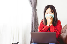 woman working from home wearing a mask