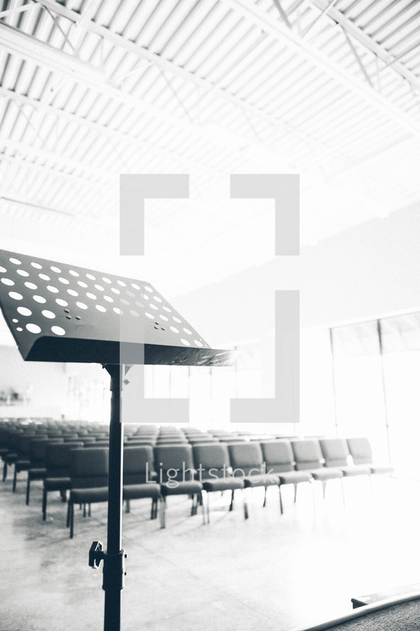 empty stand in front of empty church chairs