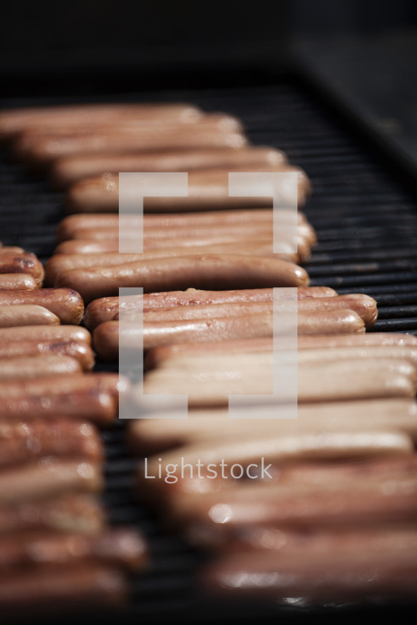 Hot dogs on a grill.