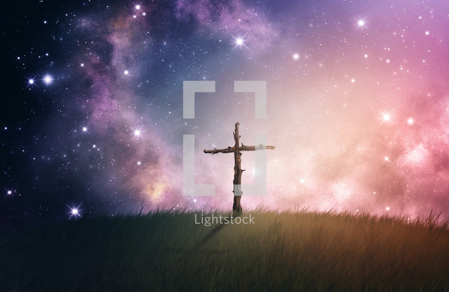 Wooden cross on a hill in the starry night sky.