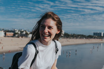 a happy woman standing on a beach