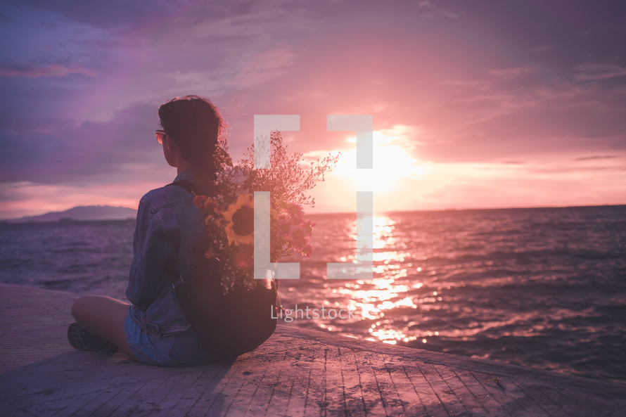 woman sitting with flowers in her backpack on a beach at sunset