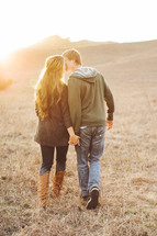 couple holding hands walking and kissing