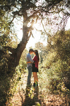 couple hugging under a tree in a forest