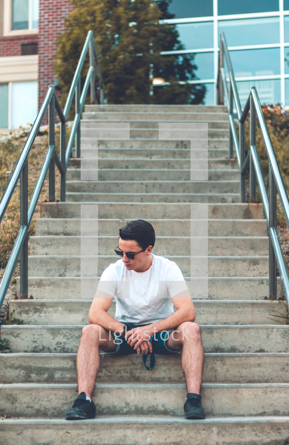 young man sitting on concrete steps