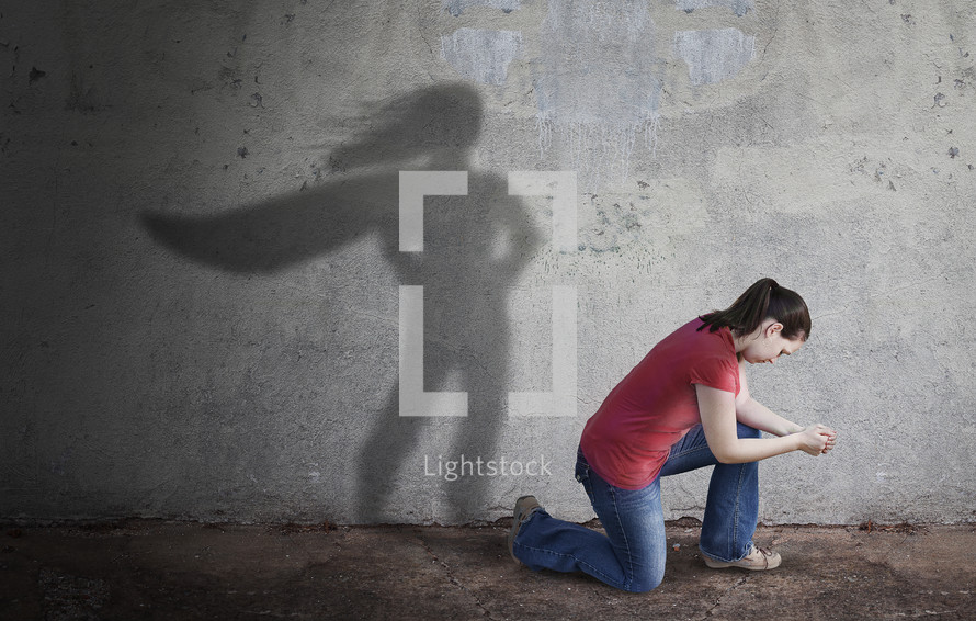 a woman praying and a shadow of a superhero