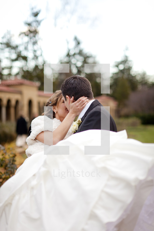 man holding and kissing his bride