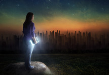 woman standing outdoors at night holding a glowing Bible looking out at a distant city