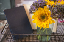 sunflowers in a vase and book in a wire basket