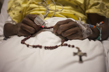 A person in a hospital bed holding a string of rosary beads.