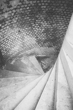 Going down a spiral staircase with brick walls.