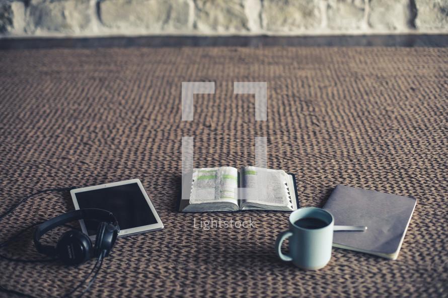 headphones, tablet, open Bible, pen, journal, and coffee cup