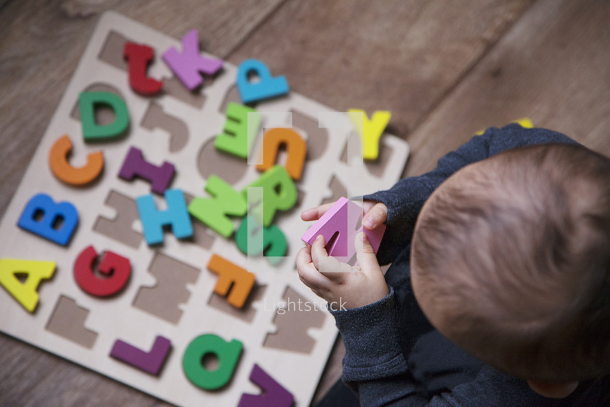 toddler with an alphabet puzzle