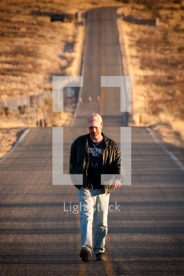 Man walking down the middle of the road.