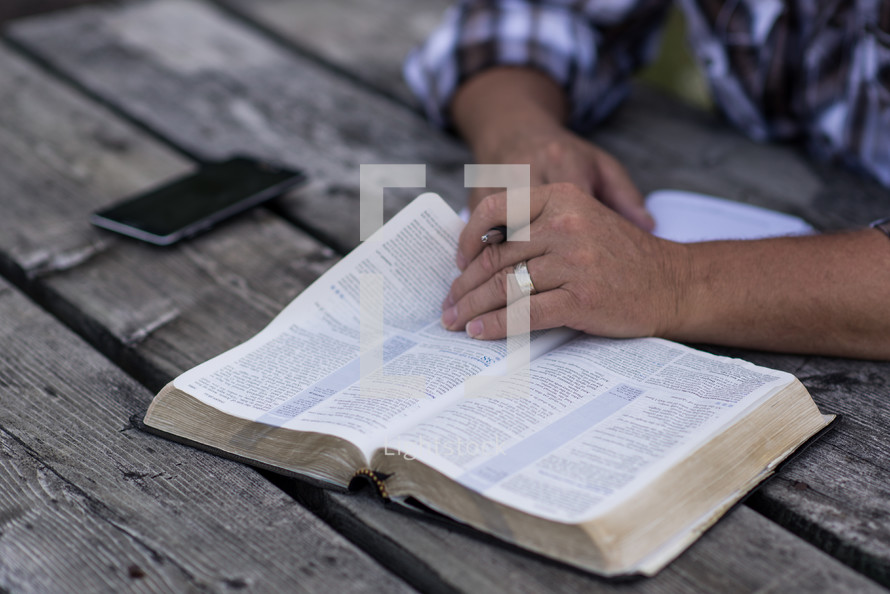 a man reading a Bible at a picnic table outdoors
