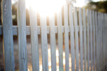 Sun shining on a white picket fence.