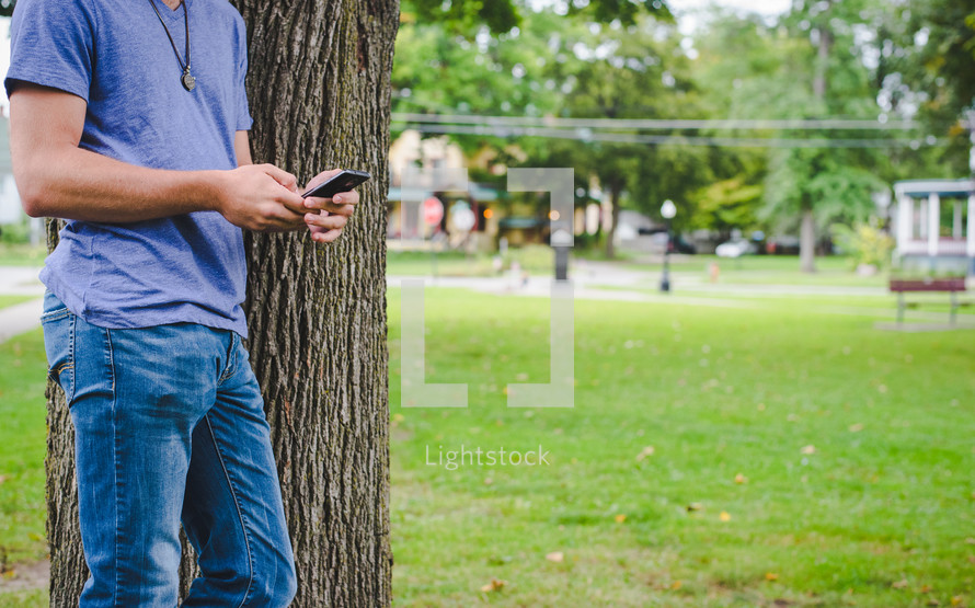 man standing beside of a tree texting