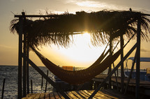 covered hammock on a dock at sunset