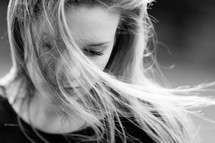 hair blowing over a woman;s face