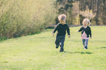 Siblings running through a field of grass.