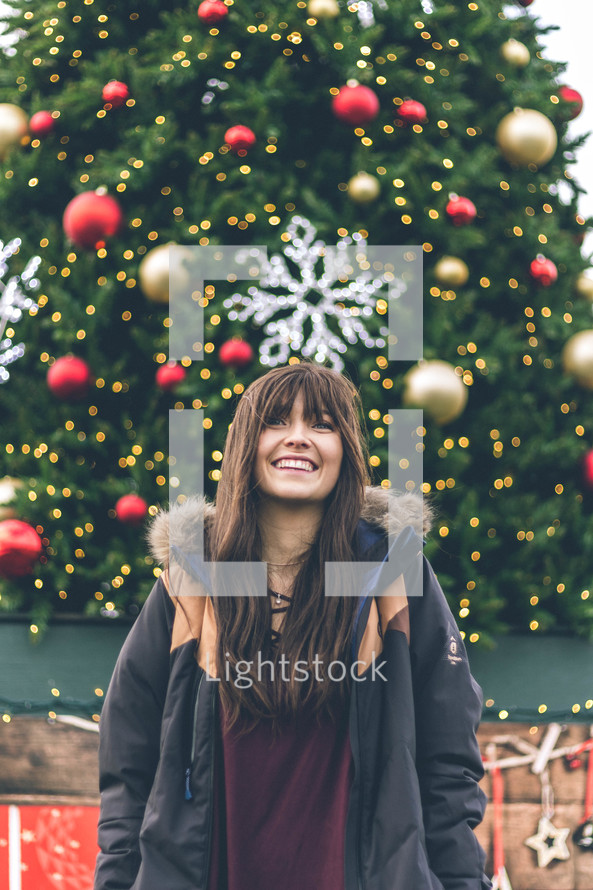 a smiling young woman standing in front of a Christmas tree