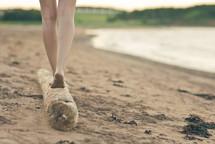 bare feet balancing on driftwood on a beach