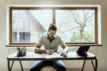 a man sitting at a desk drawing with a farm scene behind him