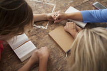holding hands in prayer around a table at a Bible study