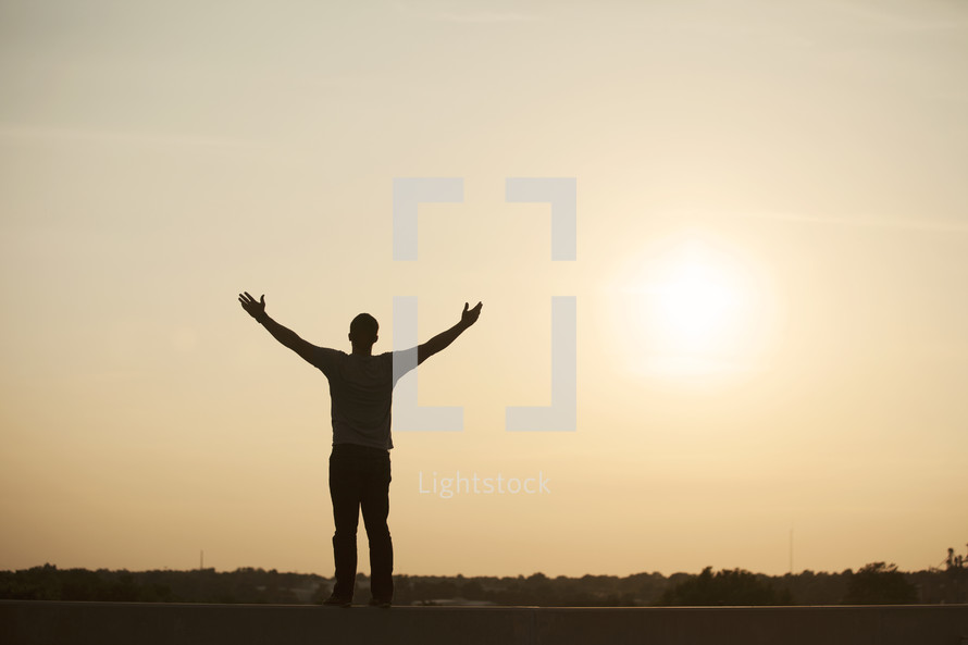 silhouette of a man standing with his arms raised in praise.