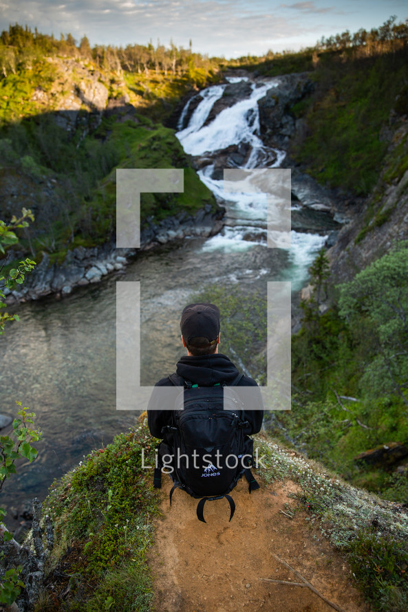 a man looking out at a waterfall