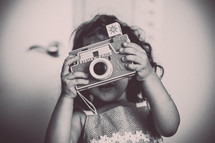 a child holding a vintage flash camera