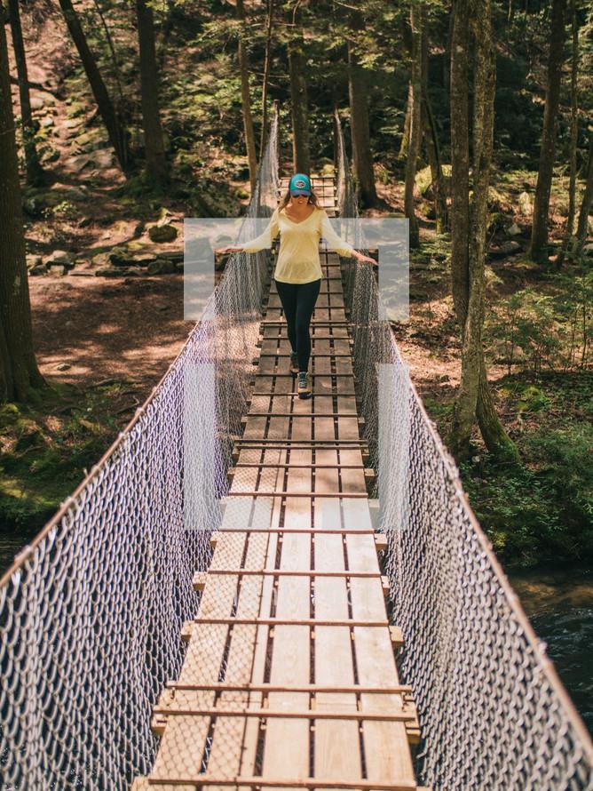 a woman walking across a swinging bridge