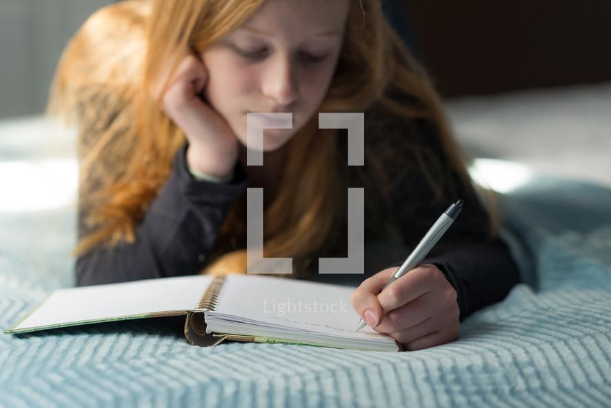 a teen girl writing in a journal