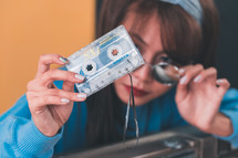 woman holding an old cassette tape