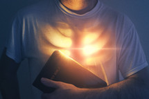 A man holds a Bible as his heart is glowing with bright lights