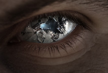 Surreal image of an eye broken with glass