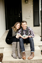 couple sitting on a step holding coffee