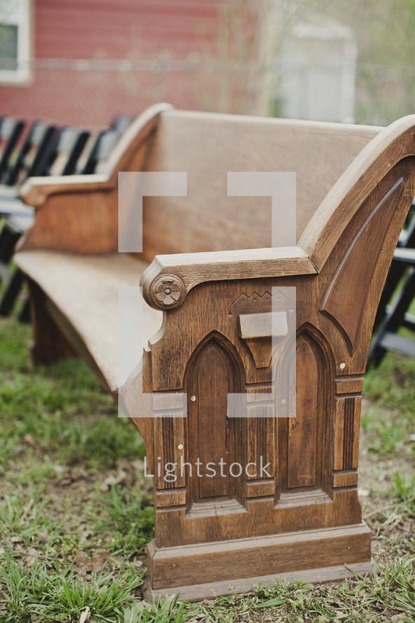 A pew sits outside a church.