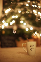A mug with the words 'Silent Night' written on it - Christmas tree in the background