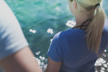 Back of a girl being baptized in a pool of water.