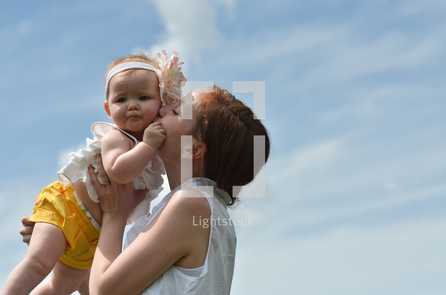 mother kissing her toddler daughter on the cheek