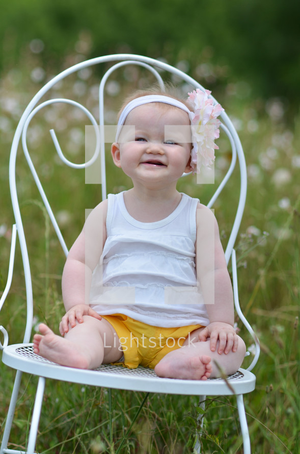 toddler girl sitting on a white chair