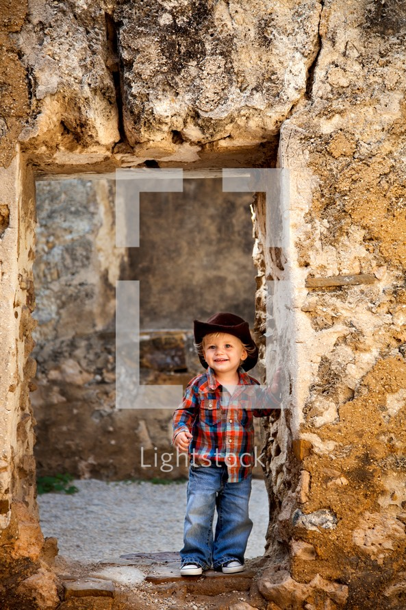smiling toddler boy in a cowboy hat