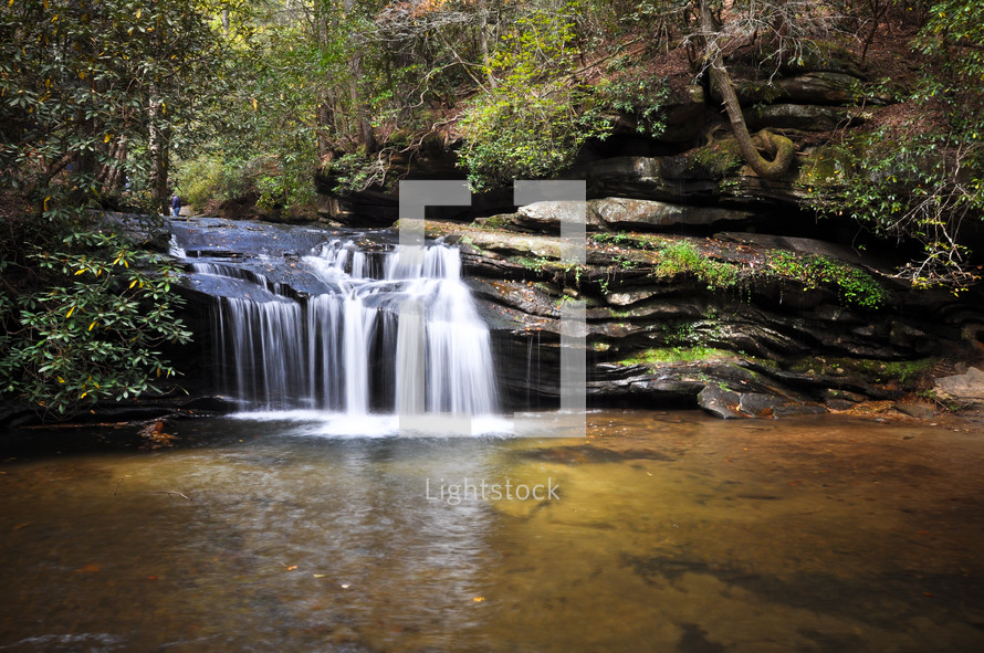 small waterfall into a swimming hole