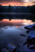 pink clouds reflecting in lake water at sunset