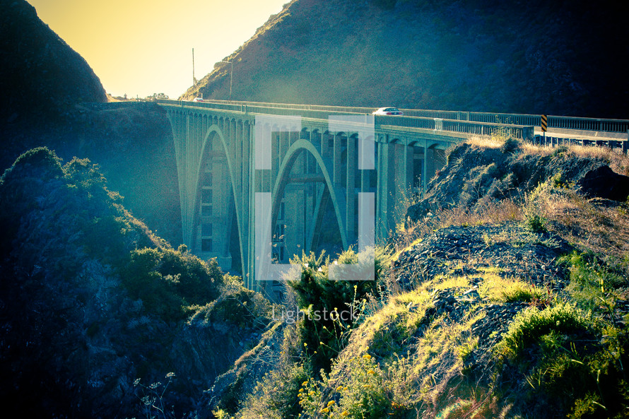 Bridge through mountainside at sunrise.